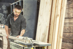 Man cutting wood with a circular saw. A young dark-haired man in a black overall and safety glasses is holding a wooden block in his hands and cutting it with a Royalty Free Stock Image