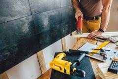Man cutting wood with electric Jigsaw. Man cutting piece of wood on the table with electric Jigsaw at home Stock Photos