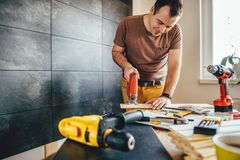 Man cutting wood with electric Jigsaw. Man cutting piece of wood on the table with electric Jigsaw at home Stock Images