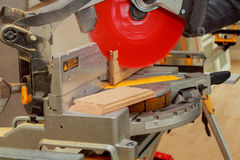 Man cutting wood on electric saw. Saw for cutting wood flooring Stock Images