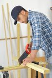 Man cutting wood with hand saw. Man cutting wood with a hand saw Stock Photos