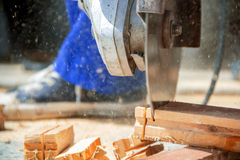 Man cutting wood with saw. Worker cuts the wood, side view Royalty Free Stock Photo