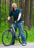 Man with cycle in park Royalty Free Stock Image