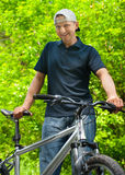 Man with cycle in park Stock Photography