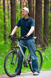 Man with cycle in park Royalty Free Stock Photos