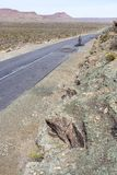 A man cycles on an open and empty Karoo road Stock Images