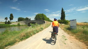 Man cycling along dirt track beside river under trees stock video footage