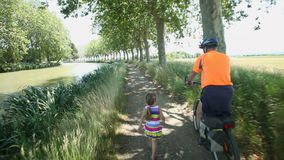 Man cycling along dirt track beside river under trees with grand daughter stock video footage
