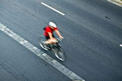 Man cycling on city street, motion Stock Images