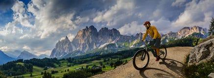 Man cycling on electric bike, rides mountain trail. Man riding on bike in Dolomites mountains landscape. Cycling e-mtb enduro