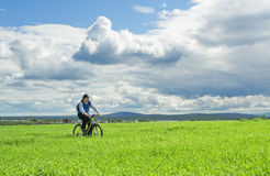 Man cycling through field Royalty Free Stock Photography