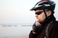 Man with cycling helmet by sea stock photography