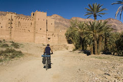 Man cycling near a small village in south Morocco Stock Photography