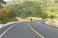 Man cycling on new road Stock Images