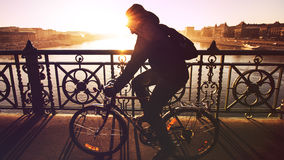 Man cycling over river bridge Royalty Free Stock Images