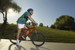 Man Cycling In Park At Dusk Stock Photography