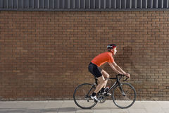 Man Cycling Past Brick Wall Stock Image
