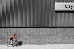 Man Cycling Past Building Royalty Free Stock Photography