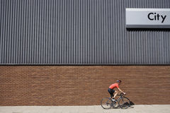 Man Cycling Past Building Royalty Free Stock Image