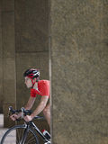 Man Cycling Between Pillars In Portico Stock Images