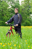 Man cyclist with bike among the green nature Royalty Free Stock Images
