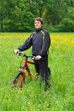 Man cyclist with bike among the green nature Stock Image