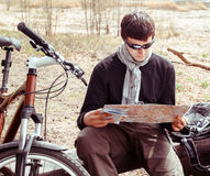 Man cyclist with map. Viewing bike path on the map Royalty Free Stock Photo
