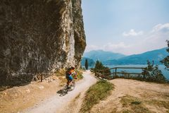 Man cyclist on a mountain bike riding on a gravel bike route at a height near the Lago di Garda in summer in Italy.  Royalty Free Stock Image