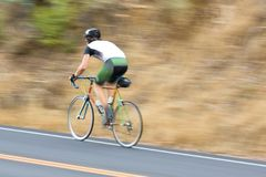 Man cyclist racing past royalty free stock photography