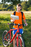 Man cyclist read the map among the summer's nature Stock Photography