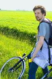 Man cyclist relaxing against the background of green fields Stock Photo
