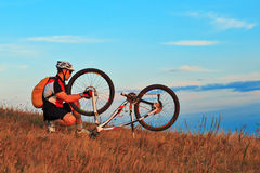 Man cyclist repairing a bike  against blue sky Royalty Free Stock Images