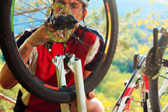 Man cyclist repairing a bike  against blue sky Royalty Free Stock Photography