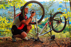 Man cyclist repairing a bike  against blue sky Stock Photo