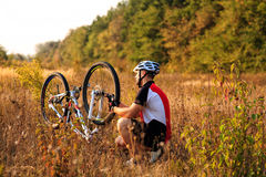 Man cyclist repairing a bike  against green nature Royalty Free Stock Photography