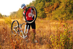 Man cyclist repairing a bike  against green nature Stock Photography