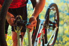 Man cyclist repairing a bike  in the wood Royalty Free Stock Photo