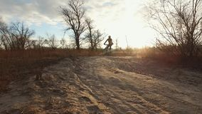 A man cyclist rides a mountain bike on a dirt road, rural road in a field at sunset in cold weather. Discipline cross. Country or mtb stock footage