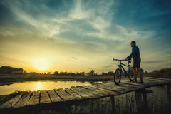 Man cyclist Rides on a wooden bridge across the river Royalty Free Stock Image