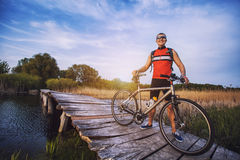 Man cyclist Rides on a wooden bridge across the river Royalty Free Stock Photography
