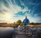 Man cyclist Rides on a wooden bridge across the river Royalty Free Stock Images