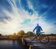 Man cyclist Rides on a wooden bridge across the river Royalty Free Stock Photos
