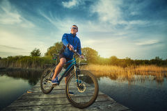 Man cyclist Rides on a wooden bridge across the river Royalty Free Stock Photo