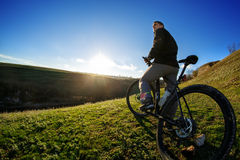 man cyclist stand with mountain bike at sunset Royalty Free Stock Images