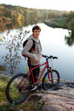 Man cyclist at sunset near the river Stock Photography