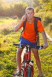 Man cyclist talking on call phone Royalty Free Stock Image