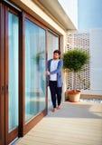 Man dörrar för öppningsglidningsexponeringsglas på uteplats hemma Arkivbild