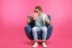 Man with 3D glasses, popcorn and beverage sitting in armchair during cinema show. On color background royalty free stock images