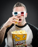 Man with 3d glasses and popcorn. Image of a man wearing 3d glasses eating popcorn stock photo