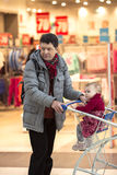 Man dad grandpa at the store with the baby in cart royalty free stock images